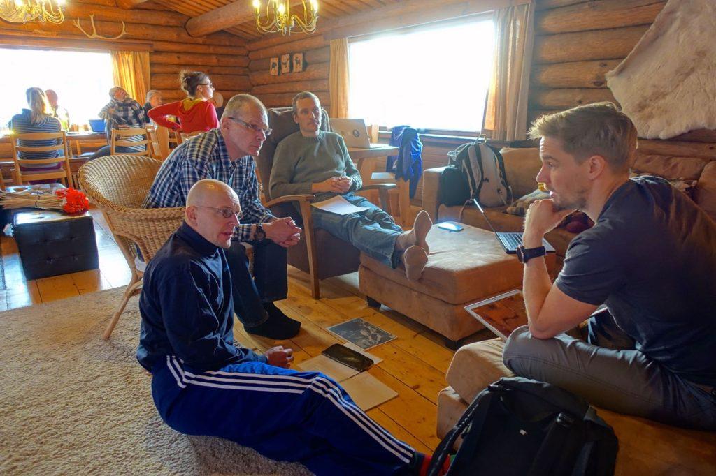 Ryhmä miehiä istuu ringissä keskustelemassa tapahtuman suunnitelmista. Taustalla muita ihmisiä pöydän ääressä. Kokous hirsirakennuksessa, jonka ikkunoista näkyy kirkas ulkoilma.